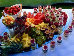 Diverse dessertjes geserveerd op een spiegel met sierlijk gesneden vers fruit