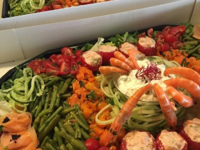 Een schotel van gemixte koude groentjes afgewerkt met tomaat crevette, gerookte zalm en gamba's